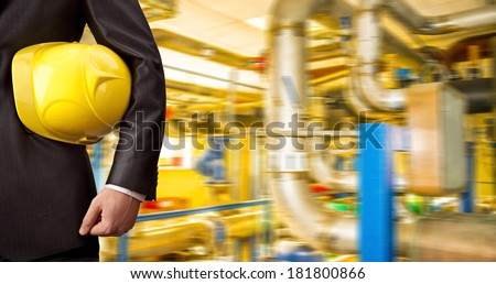 Man working in oil or gas refinery, turning on and off the pipeline valve torso and hand engineer yellow helmet for workers security construction worker No face Unrecognizable person - stock photo