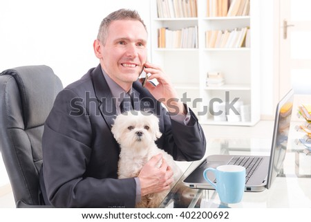 Man working in the office and holding his liitle dog. - stock photo