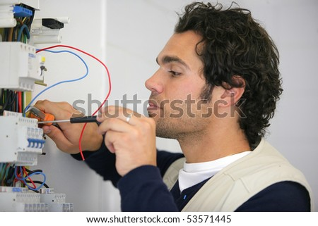 Man working on a circuit breaker - stock photo