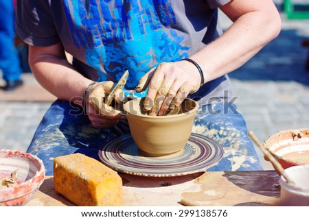 Man working on a Cpottery wheel - stock photo