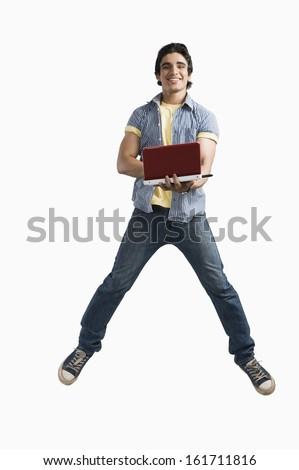 Man working on a laptop and jumping - stock photo