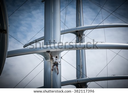 Man working on a modern sailboat masts - stock photo