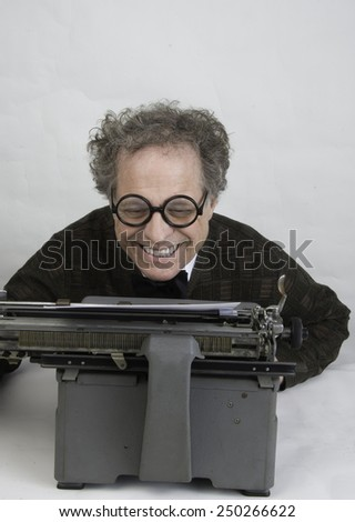 Man working on a vintage typewriter/Author Working on Typewriter/Man with glasses working on typewriter - stock photo