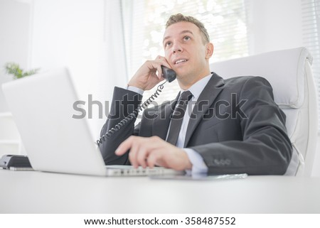 Man working on his laptop in the office.Businessman talking on the phone.He is wearing a black suit and a black tie. - stock photo