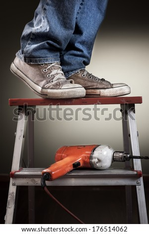 Man working on ladder with drill - stock photo