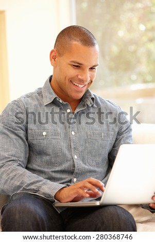 Man working on laptop at home - stock photo