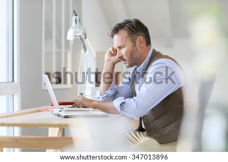 Man working on laptop computer - stock photo