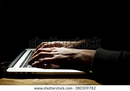 Man working on laptop in dark room - stock photo