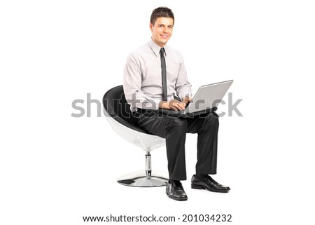 Man working on laptop seated in a modern chair isolated on white background - stock photo