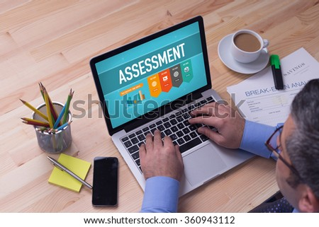 Man working on laptop with ASSESSMENT on a screen - stock photo