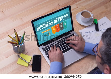 Man working on laptop with BUSINESS NETWORK on a screen - stock photo