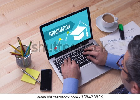 Man working on laptop with GRADUATION on a screen - stock photo