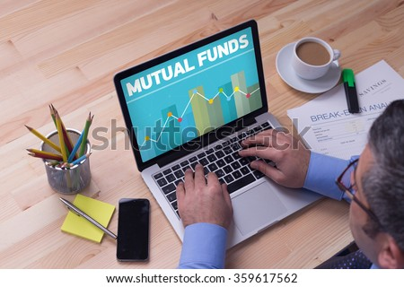 Man working on laptop with MUTUAL FUNDS on a screen - stock photo
