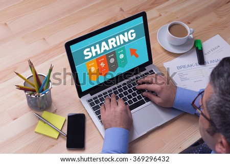 Man working on laptop with SHARING on a screen - stock photo