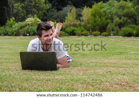 Man working on Notebook outdoors in park - stock photo