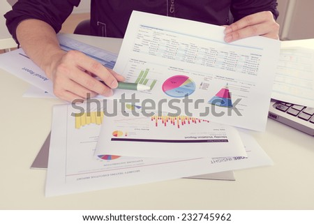 man working on paper chart, performance reporting, business concept