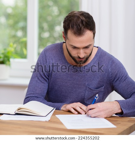 Man working on paperwork at home writing notes on a sheet of paper as he sits at a table in front of a window