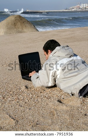 man working on portable pc on the beach