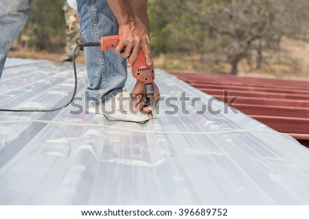Man working on roof Metal cheese in site construction - stock photo
