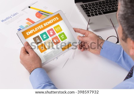 Man working on tablet with Employee Benefits on a screen - stock photo