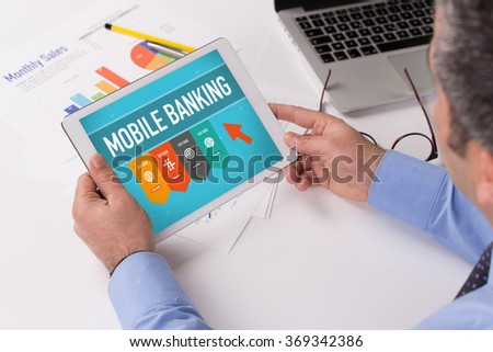 Man working on tablet with MOBILE BANKING on a screen - stock photo