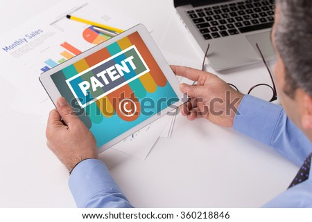 Man working on tablet with PATENT on a screen - stock photo