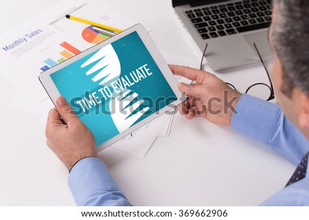 Man working on tablet with TIME TO EVALUATE on a screen - stock photo