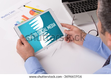 Man working on tablet with TIME TO SOCIAL MEDIA on a screen - stock photo