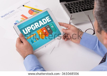 Man working on tablet with UPGRADE on a screen - stock photo