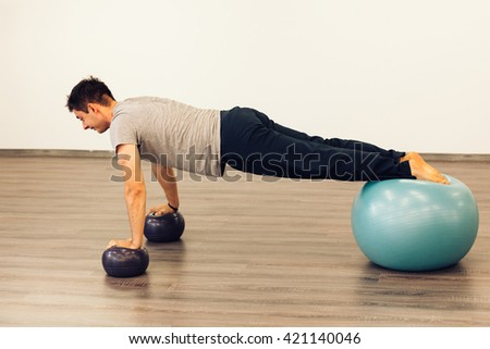 Man working out in a gym using three Pilates balls