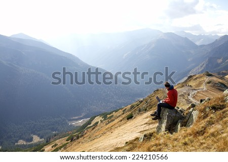 man working outdoors with laptop in High Tatras Mountains in Cloudy Day. Slovakia, Poland - stock photo