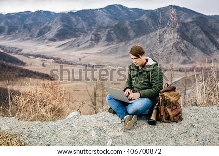 man working outdoors with laptop on the background of mountain scenery - stock photo