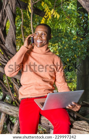 Man Working Outside. Dressing in light orange sweater with high collar, red pants,  a young black guy is sitting on wood area, smiling, making phone call, working on laptop computer.  - stock photo