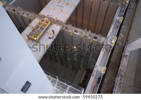 man working over precipice (cargo hold)aboard container ship during cargo operation in port terminal