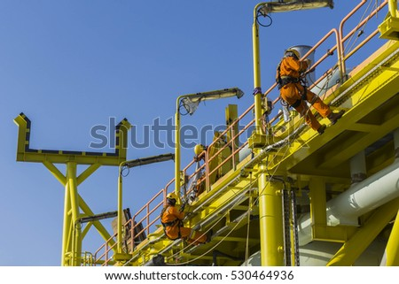 Man working overboard. Man working at height. Abseilers climbing and hanging at the edge of oil and gas platform in the middle of sea.