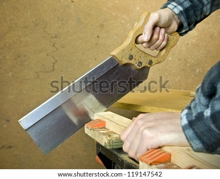 man working sawing wood on bench  in workshop with copy space - stock photo