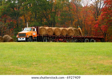 Man working to get hay up and ready for winter. - stock photo