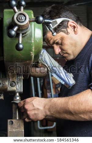 Man working with a metal pressing machine - stock photo