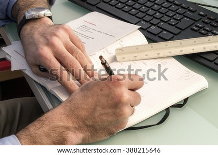 Man working with a PC writes hand notes with a pencil