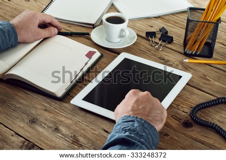 Man working with a tablet computer. The man clicks on the blank screen of the tablet closeup. Top view. Copy space. Free space for text - stock photo