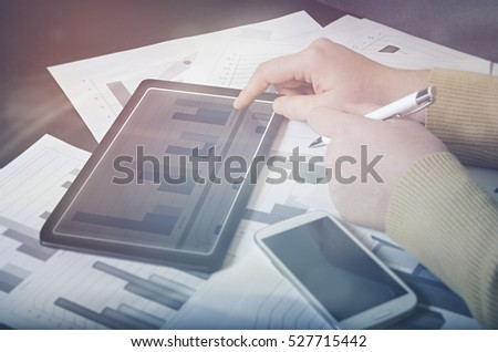 Man working with business documents on office table with smart phone and digital tablet and graph financial