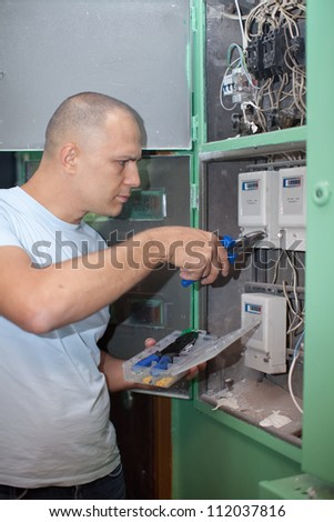 Man working with electric box at house