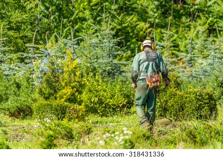 Man working with grass trimmer - stock photo