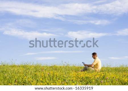 Man working with laptop in a meadow of flowers - stock photo
