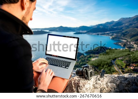 Man working with laptop on the top of mountain with beautiful landscape on background.
