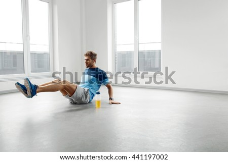Man Workout Exercises. Handsome Fitness Male Model With Athletic Muscular Body In Fashion Sportswear Doing Exercises On The Floor, Exercising Indoors. Sports, Healthy Active Lifestyle Concept