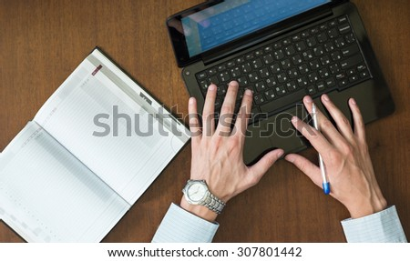 Man works with a new project. Businessman prints document on the laptop. - stock photo