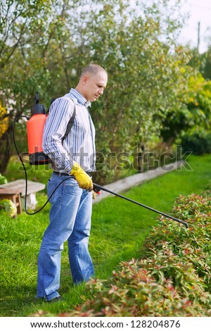 Man works with garden spray  in the yard - stock photo