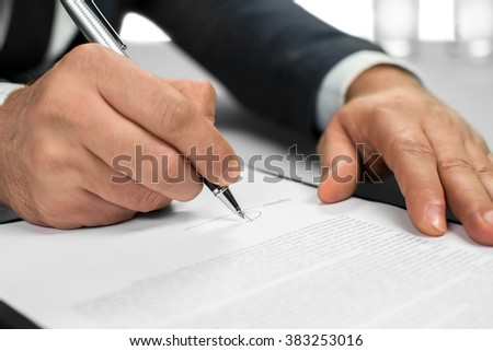 Man works with papers. The document needs a signature. Signing a letter. Official letter to a partner. - stock photo