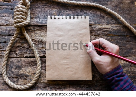 man writes a suicide note in the notebook - stock photo